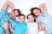 High angle portrait of caucasian happy smiling young family with two children lying down on white floor and looking at camera