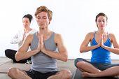 People sitting in yoga pose in fitness studio