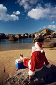 Santa Claus relaxing on the beach resting his bare feet on his cooler while looking at the view
