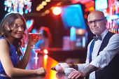 Bald male in eyeglasses and pretty young girl with drink looking at camera in the bar