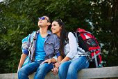 Romantic travelers with rucksacks looking at urban scene