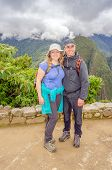 Machu Picchu, Peru - inter-ethnic couple of tourists posing for photo