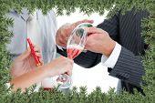 Close up of two colleague drinking champagne to celebrate christmas against green fir branches