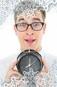 Geeky businessman holding alarm clock against snowflakes on silver