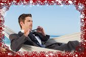 Composite image of snow frame against businessman man lying in hamock taking off his tie
