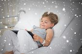 Composite image of little sick girl using digital tablet against snow falling