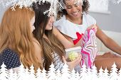Cheerful young women surprising friend with a gift against fir tree forest and snowflakes