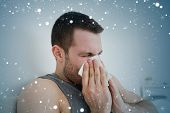 Composite image of sick man blowing his nose against snow