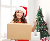 christmas, winter holidays, delivery, gesture and people concept - smiling woman in santa helper hat with parcel box showing thumbs up over living room with christmas tree background