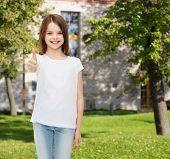advertising, summer vacation, gesture, childhood and people - smiling little girl in white t-shirt showing thumbs up over campus background