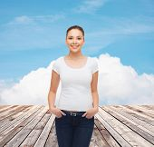 advertising, vacation and people concept - smiling young woman in blank white t-shirt over wooden berth and blue sky background