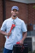 Smiling Young African American  Worker Holding Toolbox and Wrench Standing in front of AC Unit