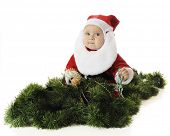 An adorable baby Santa playing with strands of Christmas beads while sitting among green garland.  On a white background.  (Motion blur on hands and beads.)