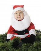 An adorable baby in a Santa suit surrounded by green Christmas garland.  On a white background.
