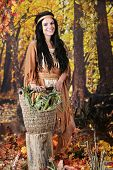 A beautiful teen Indian maiden taking a break in a colorful autumn woods.  She supports a basket full of fresh corn on an old tree stump.