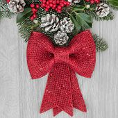 Christmas background  border with red bow decoration, holly, mistletoe, winter greenery and snow tipped pine cones over light oak background.