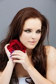 Portrait of a beautiful young brunette woman. Wearing long loose curly hair, posing with a red flower. Against grey studio background. Spa concept