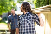 Mid adult carpenter and coworker carrying wooden planks outdoors