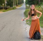 Young hitchhiking girl on countryside road. Hippie style.