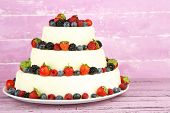 Beautiful wedding cake with berries on pink wooden background