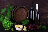 Wine in bottles and in goblet, Camembert and brie cheese, grapes and wooden barrel on wooden table on wooden background
