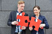 Two business people solving big red jigsaw puzzle pieces