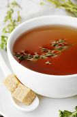Cup of tasty herbal tea with thyme, close up