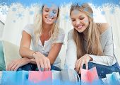 Smiling girls looking into the bags below them against snow flake frame in blue