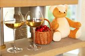 Teddy bear with wine glasses on shelf in room