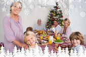 Grandmother and granddaughter standing beside the dinner table against fir tree forest and snowflakes