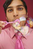 Portrait of businessman blowing bubbles