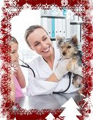 Vet with girl examining puppy in clinic against christmas themed frame