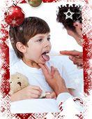 Male doctor checking little boys throat against christmas themed frame