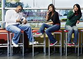 Three teenagers on stools with cell phones