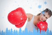 Composite image of serious woman boxing against snowflakes and fir trees in blue