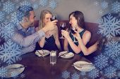 Smiling friends clinking wine glasses against snowflake frame