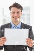 Composite image of Happy businessman holding blank page with snow falling