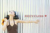 Young woman standing by recycling sign