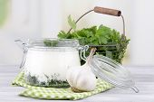 Glass round bowl of cream with a tuft of dill and pepper near it on a napkin on a wooden table