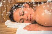 Smiling brunette lying down in a sauna against snowflakes