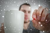 Composite image of man showing a pill and and a mug against snow falling