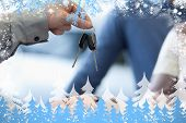 Composite image of car dealer giving keys to a customer against snow