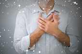 Composite image of mid section of a man with chest pain against snow