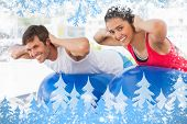 Fit couple exercising on fitness balls in gym against snow
