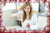 Portrait of a cute woman preparing a cake in the kitchen against snow