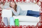 Woman relaxing on the sofa next to her shopping against snow