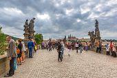 PRAGUE, CZECH REPUBLIC - 21 JUNE 2014: People walking on the Charles Bridge in Prague, Czech Republic.Charles Bridge is a famous historical bridge that crosses the Vltava river.