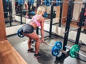 picture of squatting  - Young sexy woman in the gym doing squat with barbell - JPG