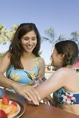 Woman applying sunscreen to daughter (7-9) at swimming pool.