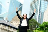 Business success - celebrating businesswoman in Hong Kong cheering business goals with arms raised up as winner. Young mixed race Chinese Asian / Caucasian female professional in Hong Kong central.